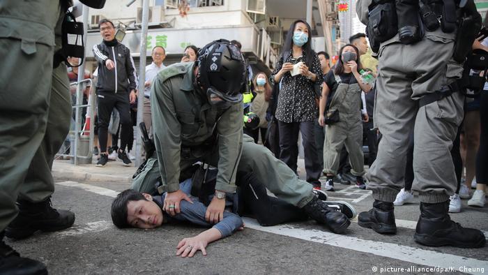 Foto de policía de Hong Kong deteniendo a manifestante.