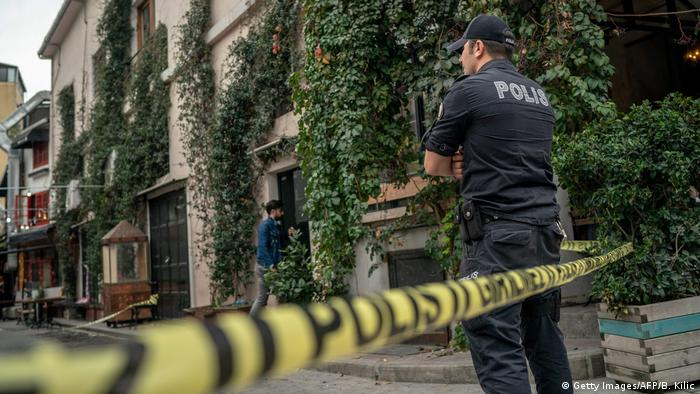 Police stand outside the ivy-covered home of James Le Mesurier in Istanbul