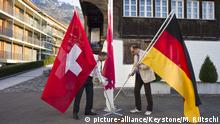 Mitglieder des Swiss German Clubs Zentralschweiz befestigen am 24. Maerz 2010 wahrend ihren Vorbereitungen zum Networking-Treffen eine deutsche, eine Schweizer und eine Obwaldner Fahne vor dem Farbhaus des Hotels Kreuz in Sachslen, Kanton Obwalden. |