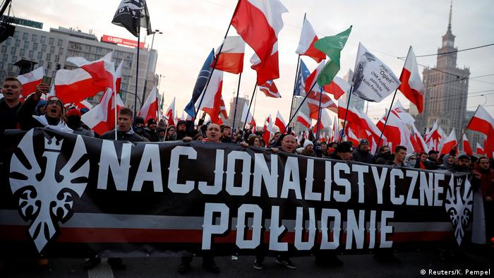 Marchers in Warsaw with a banner