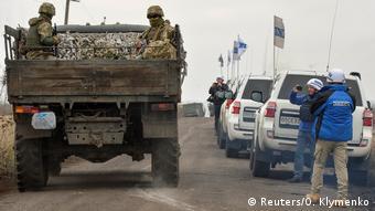 Украинские военные в грузовике рядом с машинами ОБСЕ