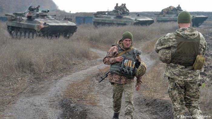 Ukrainian troops in a field with armored personnel carriers (Reuters/O. Klymenko)