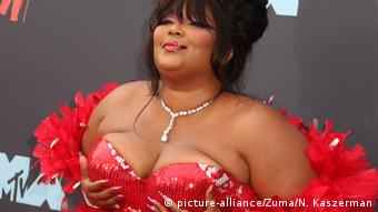 Lizzo holds her breasts in a sparkly red dress while on the red carpet for the MTV Music awards