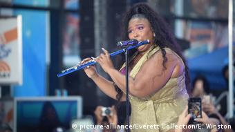 Lizzo plays the flute in front of a mic