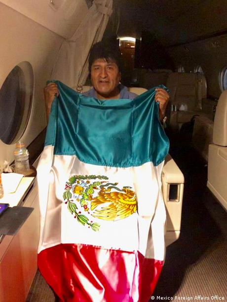 El ex mandatario boliviano posa junto a la bandera mexicana en la cabina del avión.