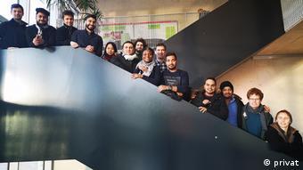 Ausländische Studierende stehen auf einer Treppe und blicken in die Kamera