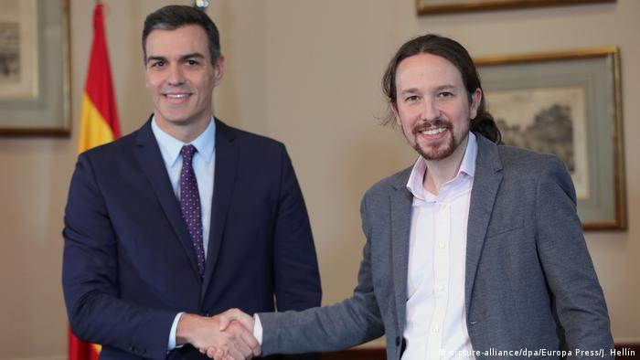 Pedro Sanchez stands on the left shaking the hand of Pablo Iglesias on the right