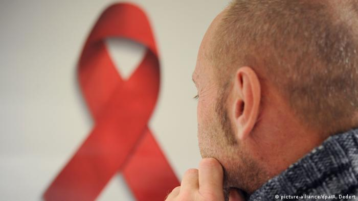 A man pictured with the HIV/AIDS red ribbon (picture-alliance/dpa/A. Dedert)