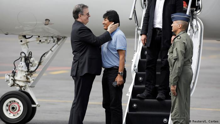 Mexico's Foreign Minister Marcelo Ebrard holds the head of Evo Morales in his hands after arriving in Mexico city