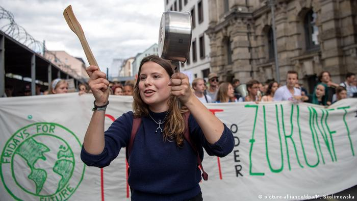 Luisa Neubauer holding a pan and a wooden spoon, leading a climate march