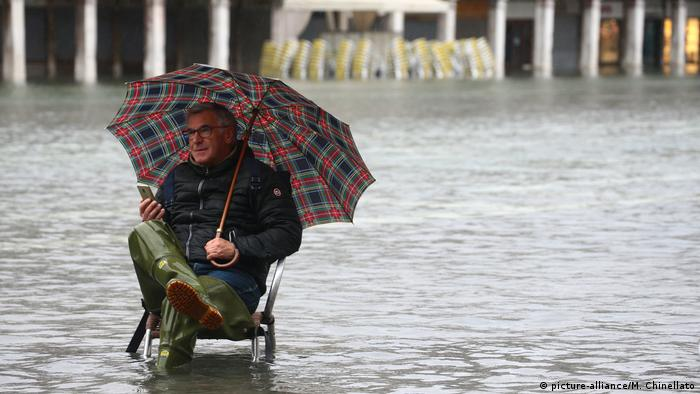 A man sits in a flooded square in Venice (picture-alliance/M. Chinellato)