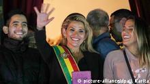 13.11.2019, Bolivien, La Paz: Boliviens Senatorin Jeanine Anez (M) trägt die Schärpe des Präsidenten und spricht vom Balkon des Quemado-Palastes winkend zu den Menschen. Nach dem Rücktritt von Boliviens Staatschef Morales hat sich die Senatorin zur Interimspräsidentin erklärt. Die 52-Jährige muss nun innerhalb von 90 Tagen eine Neuwahl organisieren. Foto: Juan Karita/AP/dpa +++ dpa-Bildfunk +++ |