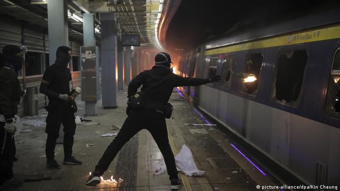 Protesters throw a molotov cocktail onto a subway car in Hong Kong