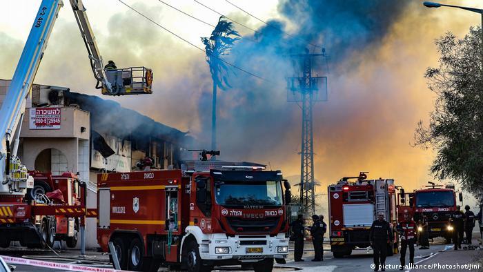 Feuerwehrleute vor einer durch Raketen in Brand geratenen Fabrik in Sderot
