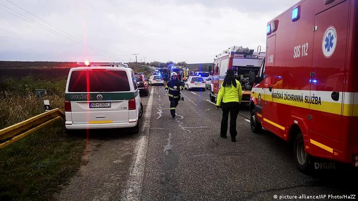 Emergency workers attend the scene after a passenger bus collided with a truck