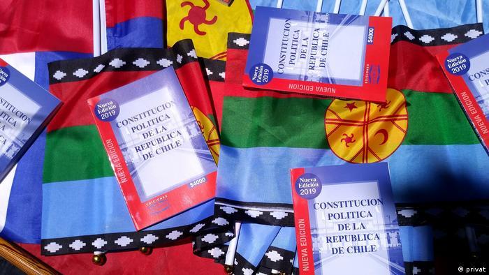 En medio de las protestas en Chile, la Constitución de 1980 se ha convertido en éxito de ventas. Aquí, en un puesto callejero en el céntrico Paseo Ahumada, junto a banderas mapuche.