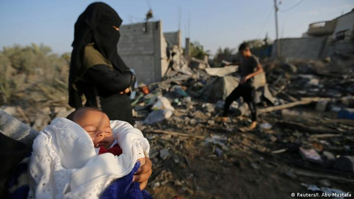 A Palestinian baby is held by a woman near the remains of a house destroyed in an Israeli air strike in the Gaza Strip