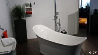 A freestanding bathtub in a bedroom with the bed reflected in a mirror