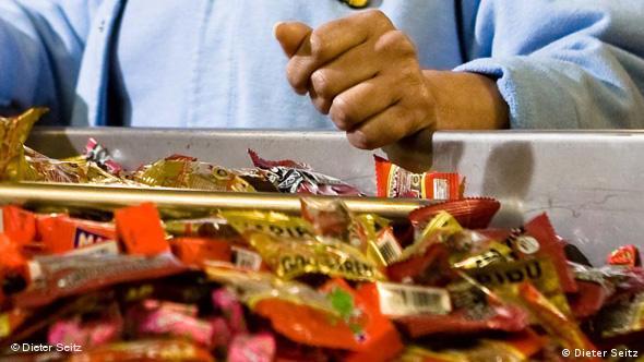 Tütchen mit Gummibären und anderen Süßigkeiten auf einem Förderband