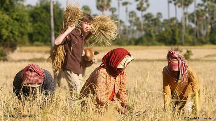 Filmszene aus SAME SAME BUT DIFFERENT mit Feldarbeitern bei der Kornernte (Delphi Filmverleih)