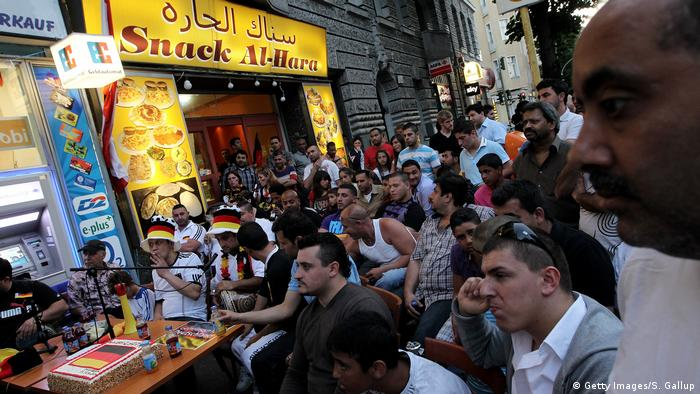 People at an middle Eastern snack shop in Berlin watch a World Cup match