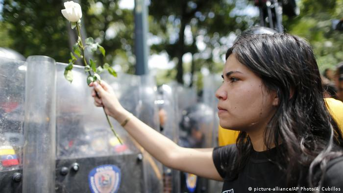 Venezuelan protester holding white rose in front of police