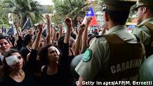 Women dressed in black and wearing eye patches, representing protesters injured with pellets shot by riot police, raise their wrists to a line of police as they take part in the so-called 'Mourning March' in Santiago on November 01, 2019, to protest against the death of 23 people after more than ten days of civil unrest. - Chile's government met with opposition leaders Thursday in a fresh bid to end deadly protests that forced the country to abandon hosting two major economic and climate summits, but leftist parties poured scorn on the efforts. The unrest started with protests against a rise in transport tickets and other austerity measures and descended into vandalism, looting, and clashes between demonstrators and police. (Photo by Martin BERNETTI / AFP) (Photo by MARTIN BERNETTI/AFP via Getty Images)
