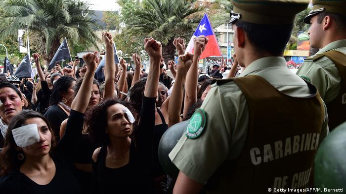 Mulheres com tapa-olhos levantam o punho diante de policiais