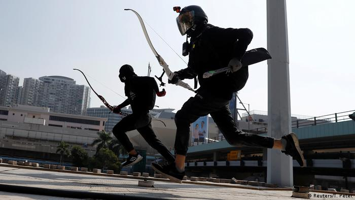 Hong Kong protesters running with bows and arrows