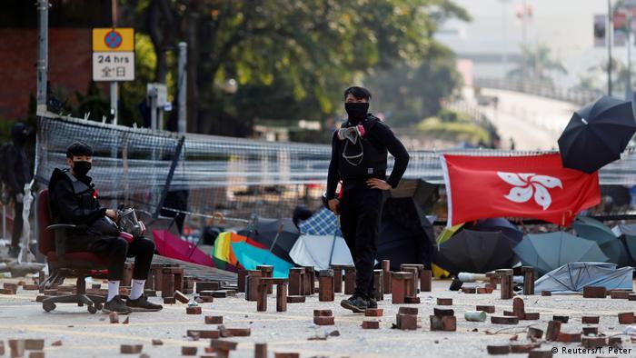 Jovens de negro e mascarados vigiam barricada com diversos tijolos no chão