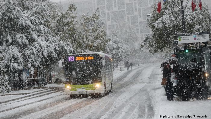 A bus drives on a snowy road (picture-alliance/dpa/F. Anterion)