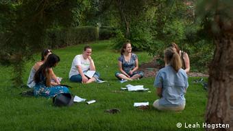Mujeres sentadas en círculo sobre el césped.