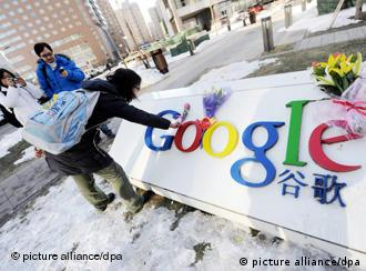 A young Chinese woman lays flowers in front of Google China headquarters in Beijing
