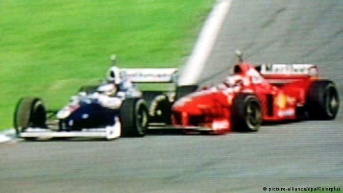 Two race cars collide on a race track.