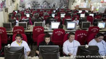 People sit at computers in an Internet cafe in Beijing