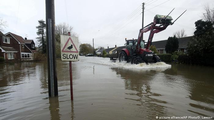 A tractor drives down a flooded road (picture-alliance/AP Photo/D. Lawson)
