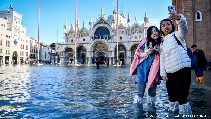 Two tourists snap a selfie in a flooded St. Mark's Square