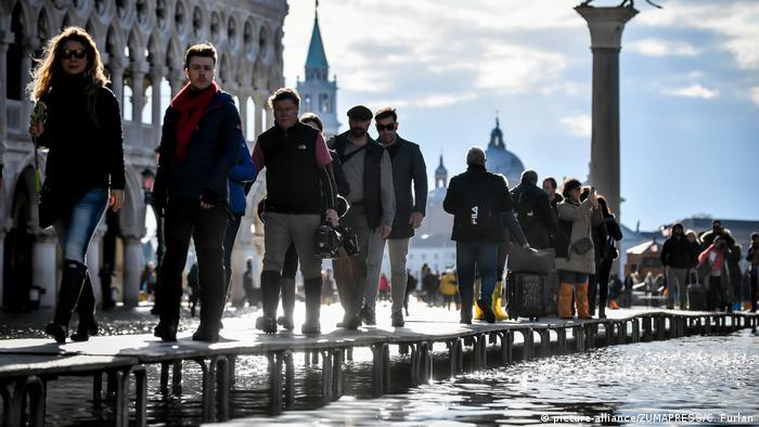 Tourists walk on temporary raised platforms to avoid flood water
