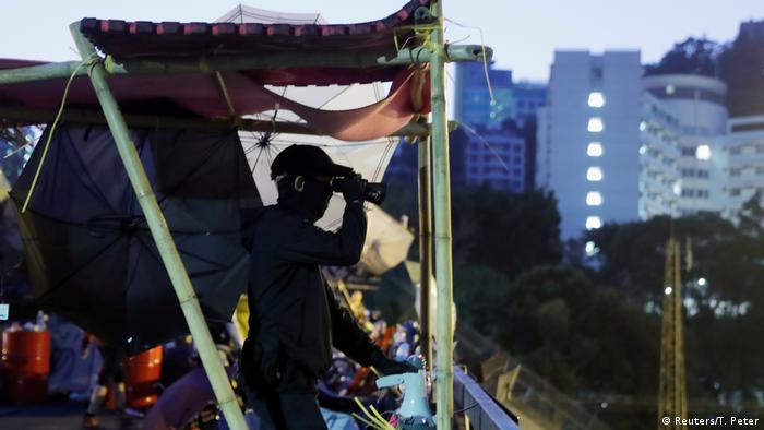 Protester examines university barricades through binoculars