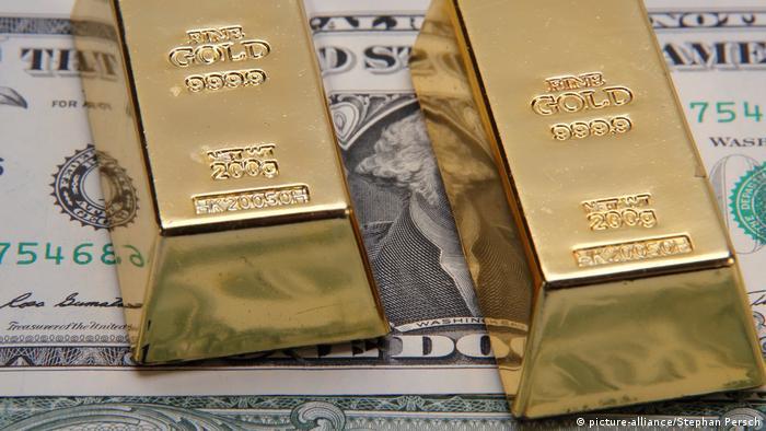 Золотые слитки на долларовых банкнотах