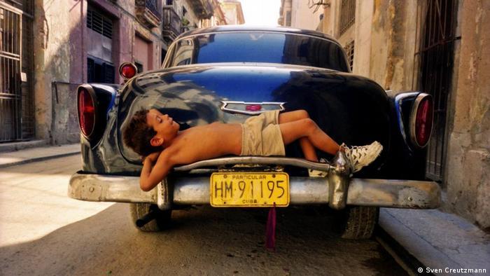 Снимка и история едновременно: 7-годишният Ернесто от Хавана се изтяга върху бронята на един американски олдтаймер в старата част на кубинската столица. Снимка, която показва колко млад е старият град.