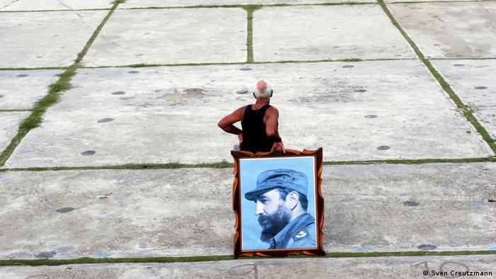 En espera, para una manifestación, un cubano, con un cuadro desmontado de una pared, como pancarta.