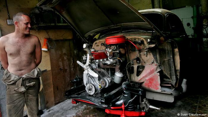 Un mecánico cubano muestra orgulloso el motor orginal de un almendrón.