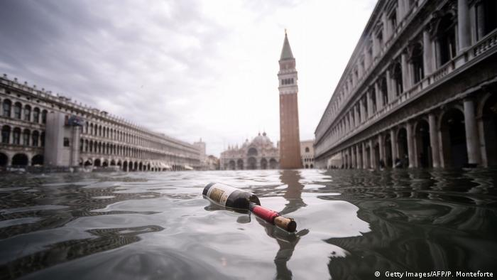 A bottle floats in a flooded Venice street