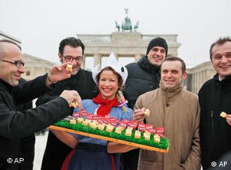 Woman presenting cheese to Chinese vistors in front of the Brandenburg gate