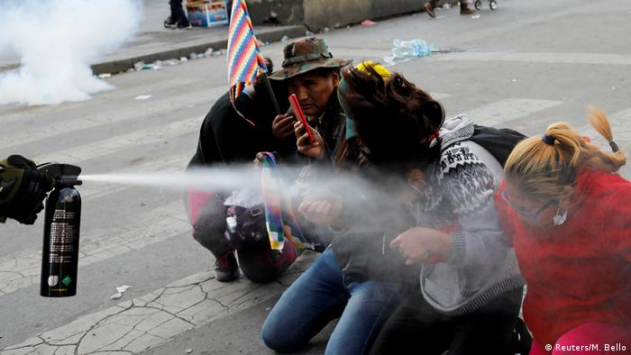Demonstrators are pepper sprayed by a member of the security forces in La Paz