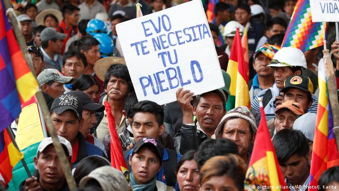 Evo Morales supporters hold a sign that reads, 'Evo, your people need you'