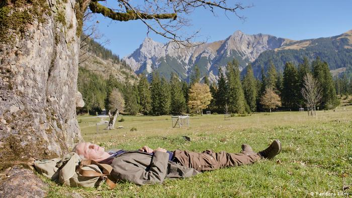 Film still But Beautiful, man lies in the grass under a tree, mountains in the background (Pandora Film )