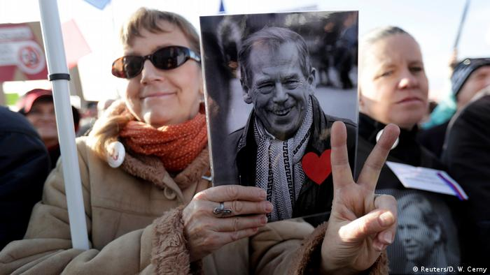 A woman holds a sign with a picture of the first Czech president, Vaclav Havel