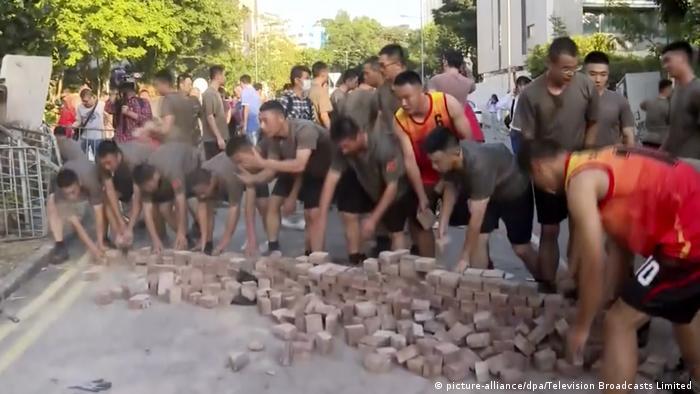 Soldados chineses ajudam a limpar ruas bloqueadas com entulhos